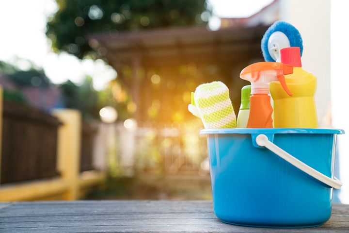 A bucket with cleaning supplies is sitting on a wooden table outdoors in front of a house.